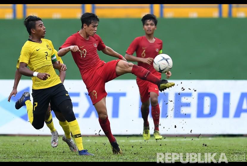Pesepak bola Indonesia Alfendra Dewangga (tengah) berebut bola dengan pesepak bola Malaysia Muhammad Mukhairi Ajmal (kiri) saat bertanding pada semifinal Piala AFF U-18 di Stadion Go Dau di Provinsi Binh Duong, Vietnam, Sabtu (17/8/2019).