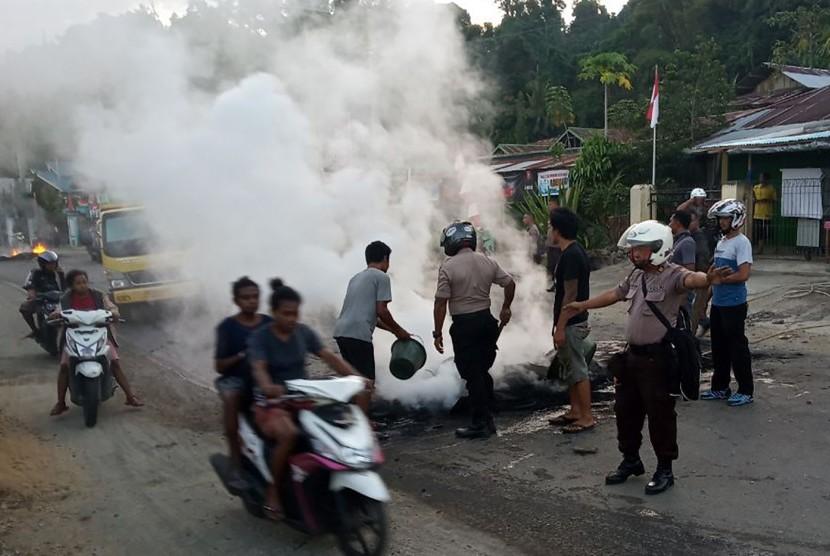 Petugas kepolisian bersama warga membersihkan ban yang dibakar seusai aksi di Jl.Essau Sesa Manokwari, Papua Barat, Senin (19/8/2019).