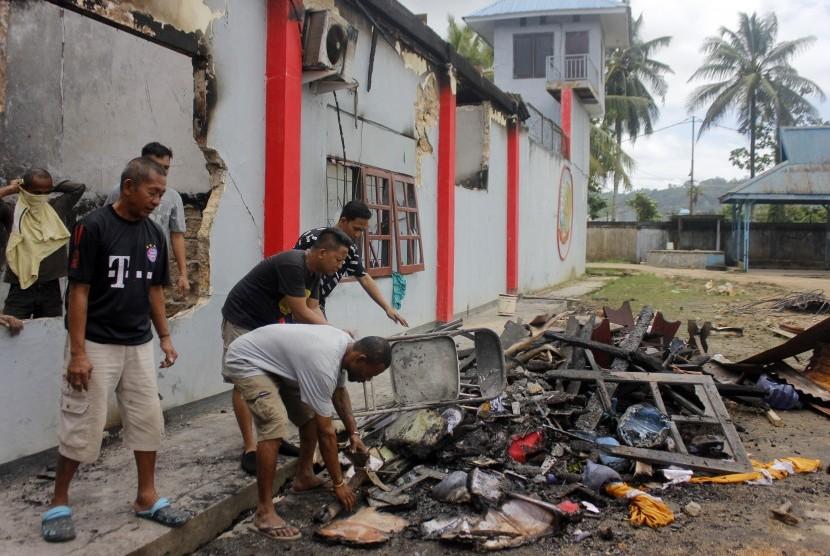 Warga binaan membersihkan sisa kebakaran di kantor Lembaga Pemasyarakatan (Lapas) Kelas II B Sorong, Papua Barat, Rabu (21/8/2019).