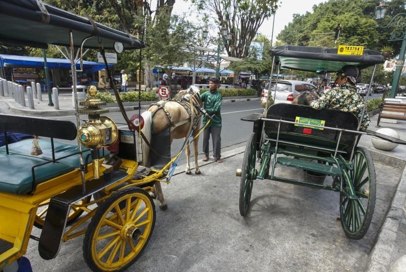 Wisatawan menaiki andong di kawasan Malioboro, DI Yogyakarta, Jumat (23/8/2019).