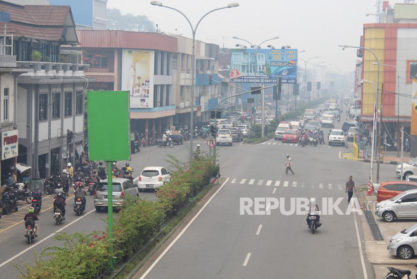 Sejumlah pengendara melintasi jalan yang diselimuti kabut asap di Pontianak, Kalimantan Barat, Selasa (10/9/2019).