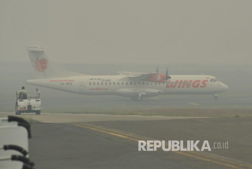 Sebuah pesawat udara bersiap lepas landas di Bandara Sultan Thaha yang diselimuti kabut asap karhutla, Jambi, Senin (23/9/2019). Kota Jambi kembali terpapar kabut asap yang bertambah pekat dalam tiga hari terakhir