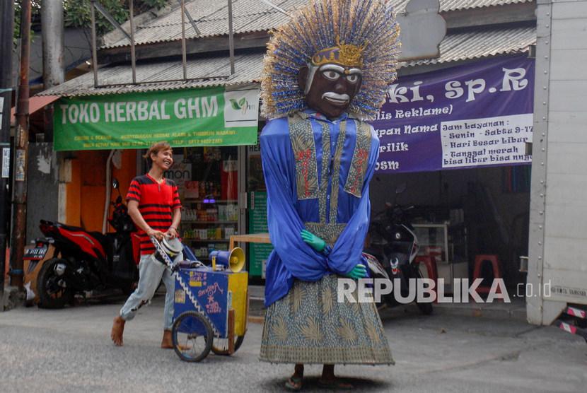 Pengamen ondel-ondel menari melintasi Jalan Raya Keadilan, Depok, Jawa Barat, Selasa (25/9/2019).