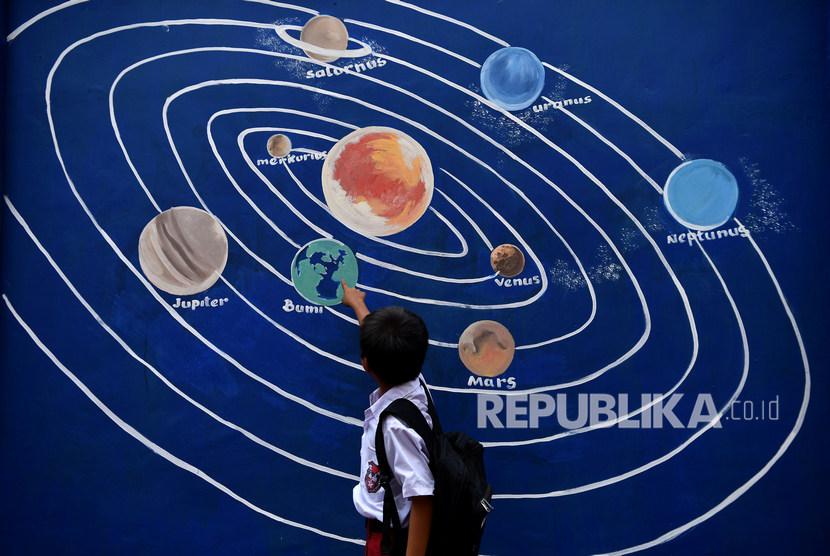 Pelajar melihat mural tentang tata surya di kawasan Pademangan Timur, Jakarta Utara, Senin (11/11/2019).