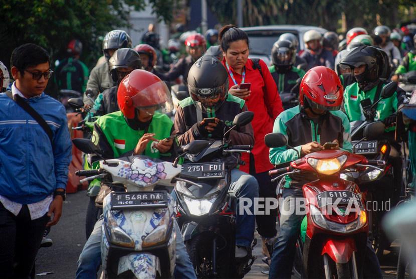 Pengemudi ojek online menunggu penumpang di kawasan Paledang, Kota Bogor, Jawa Barat, Selasa (19/11/2019).