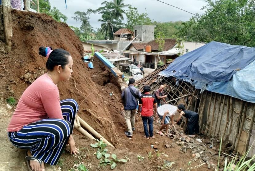 Warga bergotong royong membersihkan sisa material longsor yang menimpa sebuah rumah di Kampung Cimanggala, Kelurahan Gunung Tandala, Kecamatan Kawalu, Kota Tasikmalaya, Senin (16/12).