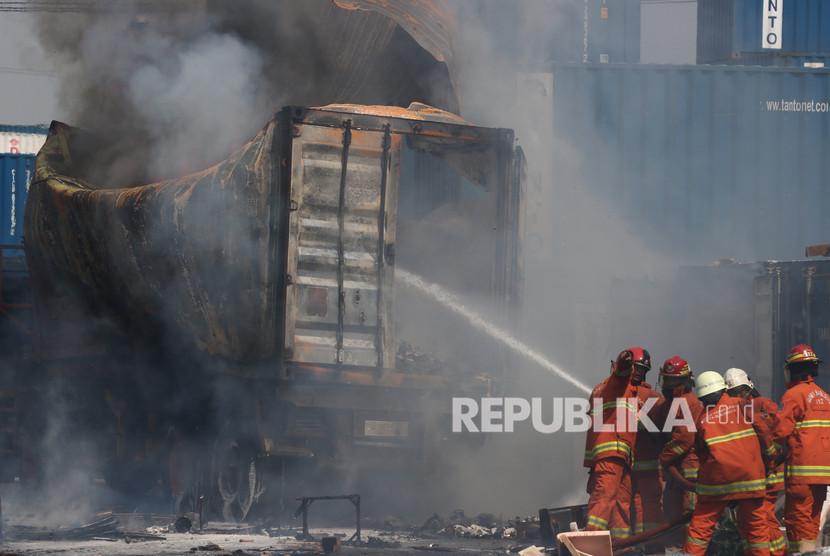 Petugas Dinas Pemadam Kebakaran Kota Surabaya memadamkan kontainer di atas truk yang terbakar di Depo Tanto Jalan Tanjung Emas No 1 Surabaya, Jawa Timur, Jumat (20/12/2019).