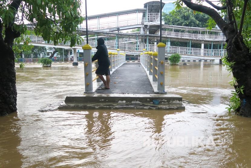 Seorang warga berada di atas jembatan Sungai Ciliwung yang meluap dan banjir menggenangi kawasan Pasar Baru di Jakarta Pusat, Kamis (2/1/2020). Kawasan perbelanjaan Pasar Baru, Jakarta Pusat pada Kamis (2/1), terpantau sepi.