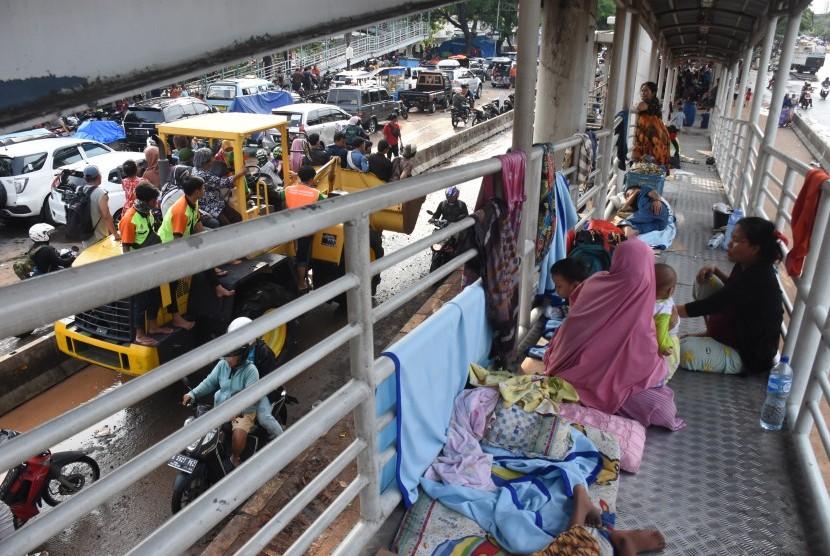 Warga menungsi di Halte Transjakarta Jembatan Baru, Daan Mogot, Jakarta Barat, Kamis (2/1/2020).