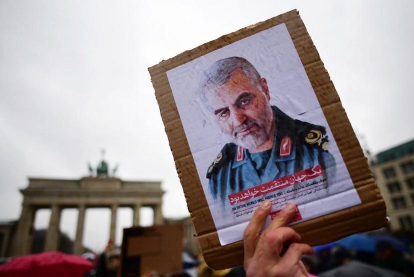 Seorang pemrotes memegang sebuah kardus yang memperlihatkan potret Letnan Jenderal Komandan Revolusioner Iran (IRGC) dan komandan Pasukan Quds Qassem Soleimani selama demonstrasi di depan Gerbang Brandenburg, dekat dengan kedutaan AS di Berlin, Jerman, 4 Januari 2020
