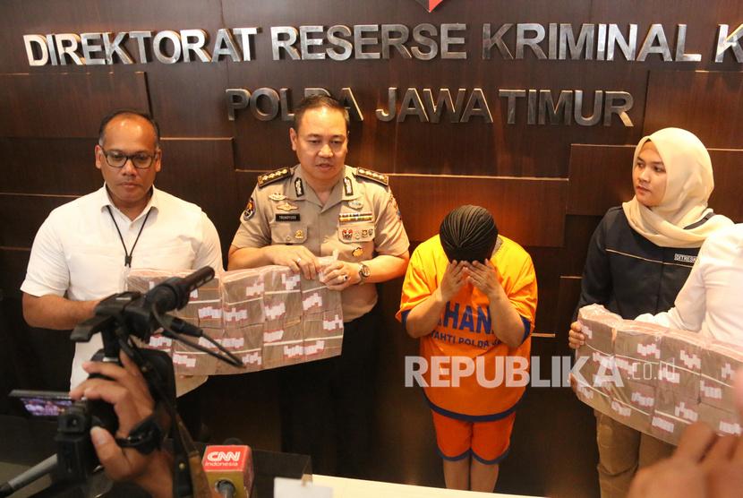 Polisi menunjukkan tersangka berinisial SW beserta barang bukti saat ungkap kasus investasi ilegal MeMiles yang dikelola PT Kam and Kam di Mapolda Jawa Timur, Surabaya, Jawa Timur, Jumat (17/1/2020).