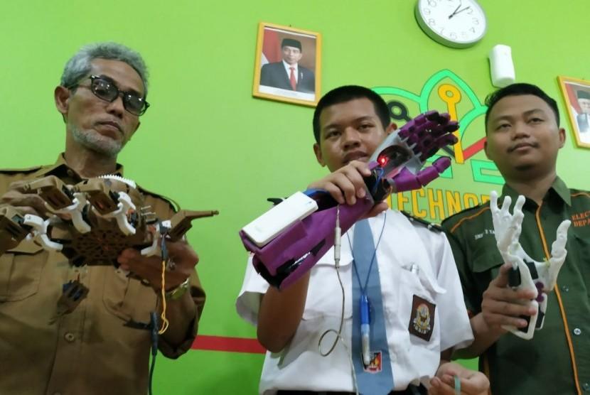 Alwan Hanif Ramadhan (16 tahun) menunjukkan lengan robot buatannya di sekolahnya, SMKN 2 Tasikmalaya, Kota Tasikmalaya, Selasa (21/1).