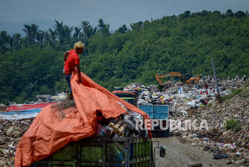 Petugas melakukan bongkar muat sampah di Tempat Pembuangan Akhir (TPA).