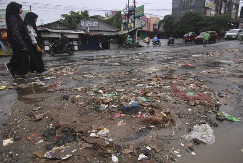 Sejumlah warga melintasi sampah yang berserakan di Jalan Mampang, Sawangan, Depok, Jawa Barat, Sabtu (8/2/2020).