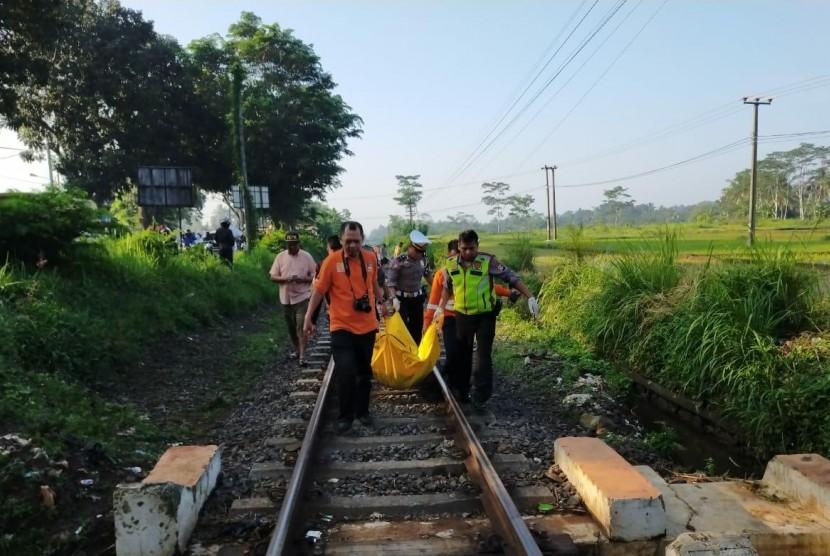 Polisi melakukan evakuasi jenazah korban tertabrak kereta api.