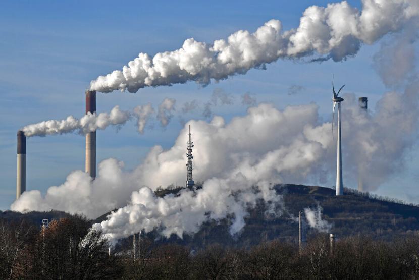 Pembangkit listrik tenaga batu bara berdiri bersebelahan dengan generator angin di Gelsenkirchen, Jerman. Dunia mencapai rekor terbaru karbon dioksida yang memerangkap panas di atmosfer meski emisi berkurang karena pandemi covid-19.