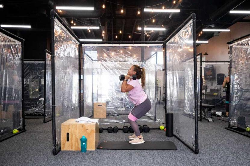 Seorang siswa berlatih fitness atau kebugaran dikelilingi oleh lembaran plastik untuk memastikan jarak sosial di pusat kebugaran. Ahli kesehatan ingatkan bugar dan aktif lebih penting dari sedikit kelebihan berat