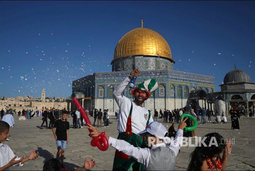 Pria berkostum badut bermain bersama anak-anak dengan latar Masjid Kubah Batu usai melaksanakan sholat Idul Fitri di Kompleks Masjid Al Aqsa, Yerusalem, Kamis (13/5).