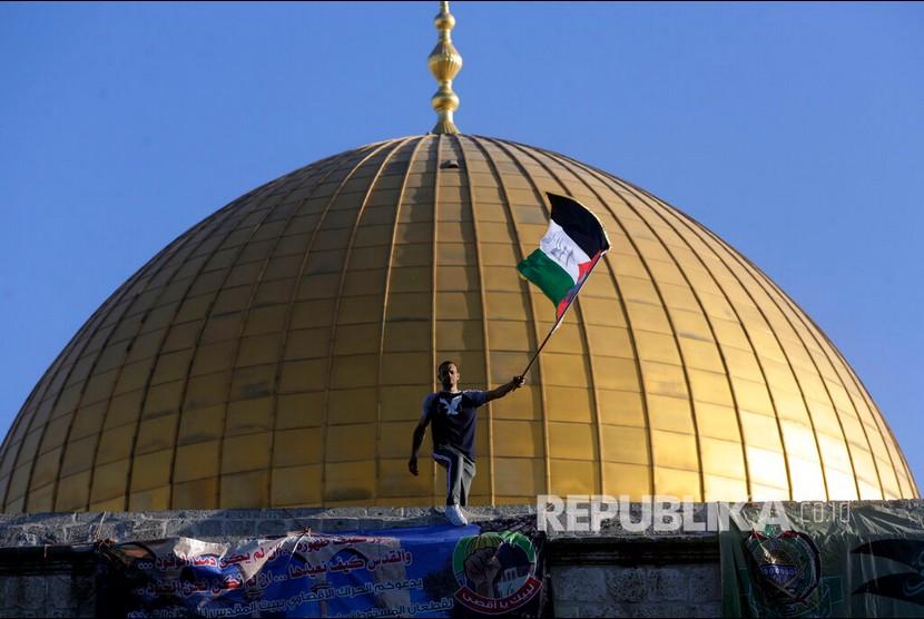 Seorang pemuda mengibarkan bendera Palestina dengan latar Masjid Kubah Batu usai melaksanakan sholat Idul Fitri di Kompleks Masjid Al Aqsa, Yerusalem, Kamis (13/5).