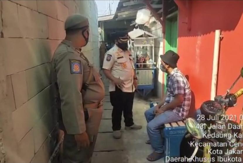 Petugas Satpol PP Jakarta Barat menemui pedagang bakso keliling yang sempat melayani penghuni hotel isolasi Covid-19, Rabu (28/7).