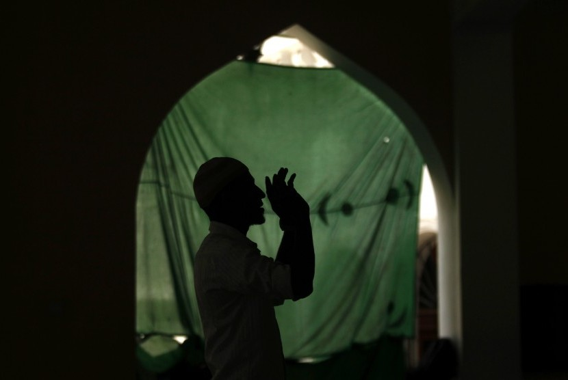 A Muslim man is silhouetted as he prays at a mosque during the month-long fasting on Ramadan in Colombo Download :