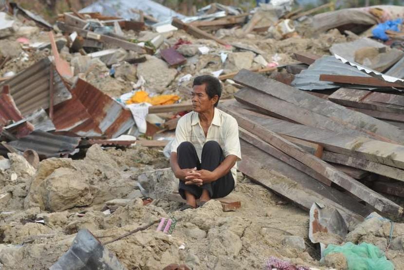 Abdullah (64), salah satu korban selamat dari bencana alam gempa dan pencairan tanah (likuifaksi) duduk disekitar puing rumahnya yang hancur dan tertimbun lumpur di Kelurahan Petobo, Palu, Sulawesi Tengah, Kamis (11/10).