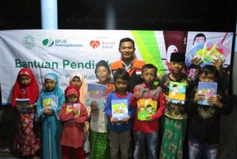 Adik binaan Rumah Belajar Mata Tunas, yang merupakan program pendidikan Rumah Zakat di desa Berdaya Suci, Jember, mendapatkan bantuan buku tulis sebagai bekal duduk di kelas baru.