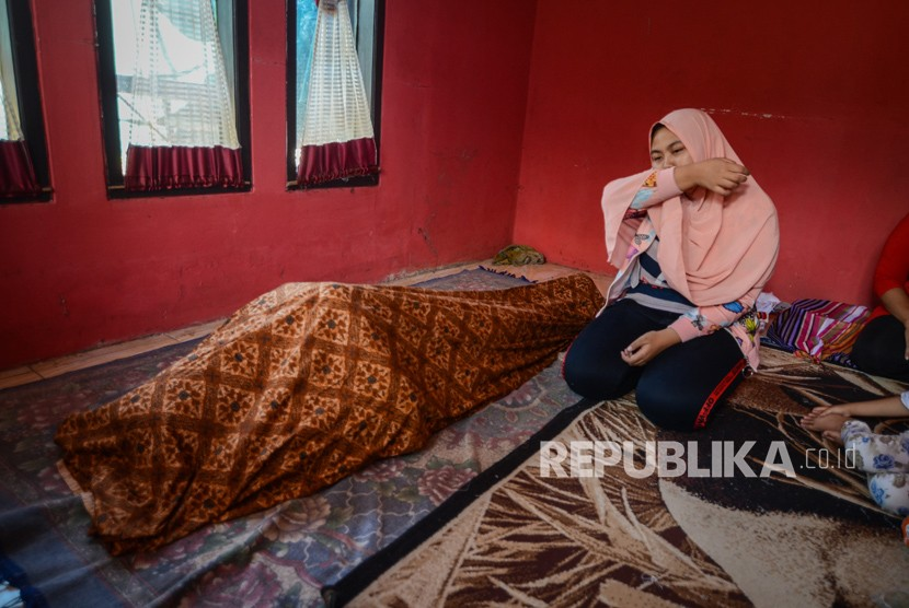 Adik dari korban minuman keras (miras) oplosan menangis di rumah duka setelah dibawa dari Rumah Sakit Umum Daerah Cicalengka (RSUD), Kabupaten Bandung, Jawa Barat, Jumat (13/4).