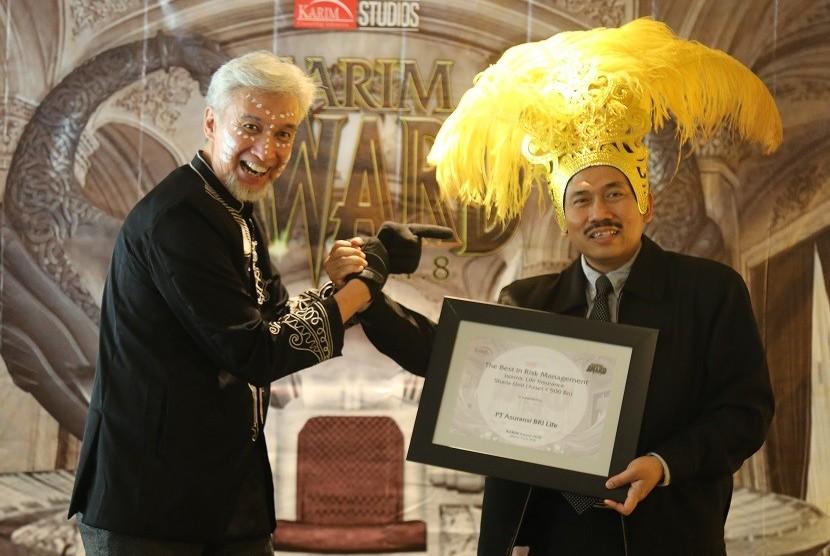 """Adiwarman A Karim, Founder Karim Consulting Indonesia (kiri) menyerahkan penghargaan """"1st Rank in Risk Management Islamic Life Insurance"""" kepada Hanung Budiarto, Head of Risk Management BRI Life."""