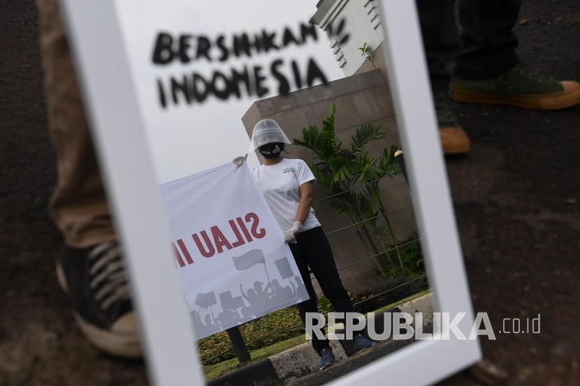Aktivis Gerakan #BersihkanIndonesia membawa cermin saat mengikuti aksi di depan kompleks Parlemen, Senayan, Jakarta, Selasa (14/7/2020). Aksi tersebut untuk menolak Omnibus Law RUU Cipta Kerja.