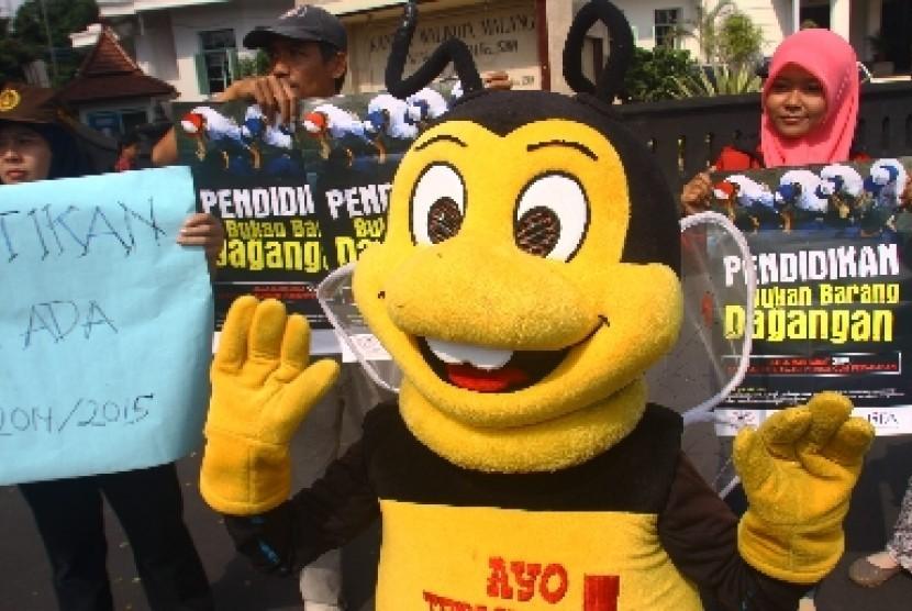 Aktivis Malang Corruption Watch (MCW) membawa poster saat berunjukrasa di depan Balaikota Malang, Jawa Timur. (Ilustrasi)