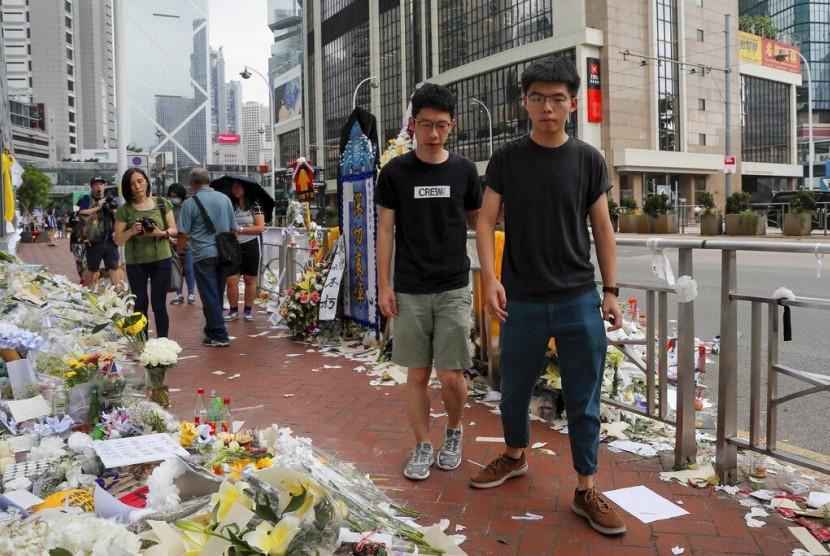 Aktivis prodemokrasi Hong Kong Joshua Wong (kanan) dengan ditemani Nathan Law memberi penghormatan pada seorang demonstran yang jatuh dan meninggal saat protes menentang RUU ekstradisi di Hong Kong, Senin (17/6).