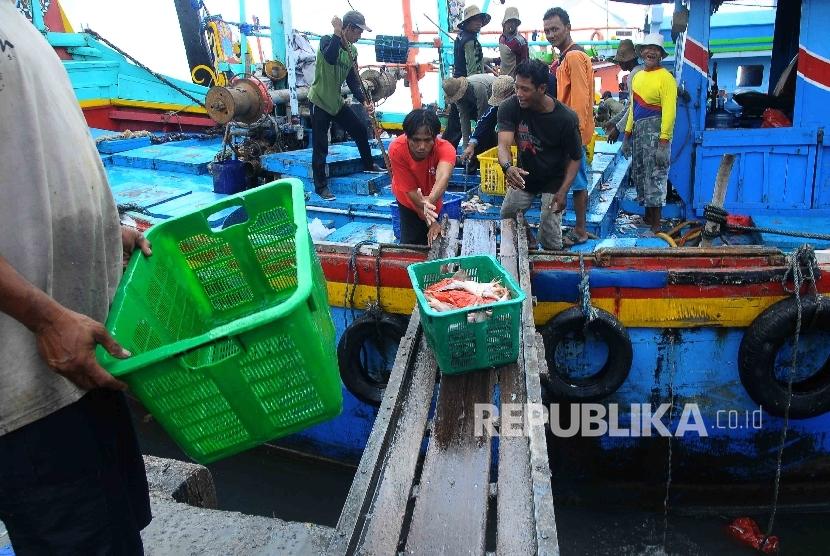 Aktivitas pekerja membongkar muat ikan hasil tangkapan nelayan di Tempat Palelangan Ikan (TPI) Brondong, Lamongan, Jawa Timur, Kamis (6/10)