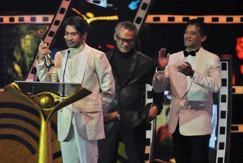 Aktor Reza Rahadian (kiri) memperlihatkan Piala Citra untuk kategori pemeran utama pria terbaik dalam film Habibie & Ainun
