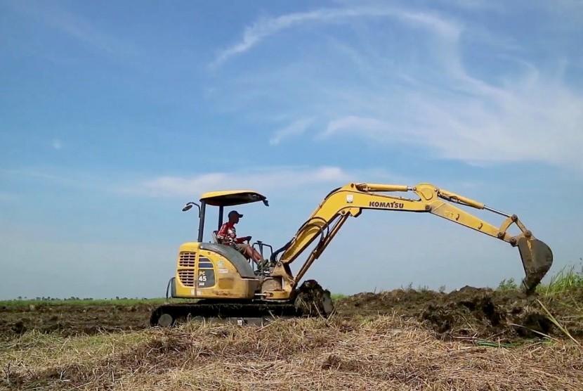 Alat berat membuka lahan untuk pertanian rawa.