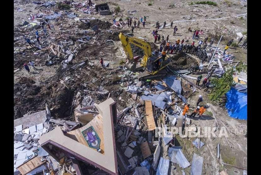 Alat berat mencari korban yang tertimbun lumpur akibat pencairan (likuifaksi) tanah yang terjadi di Desa Jono Oge, Sigi, Sulawesi Tengah, Kamis (4/10).