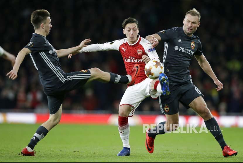 Aleksandr Golovin (kiri) dan  Aleksei Berezutski (kanan) mengepung Mesut Ozil (tengah), pada pertandigan perempat fiinal Liga Eropa di Emirates stadium, London, Jumat (6/4) dini hari.