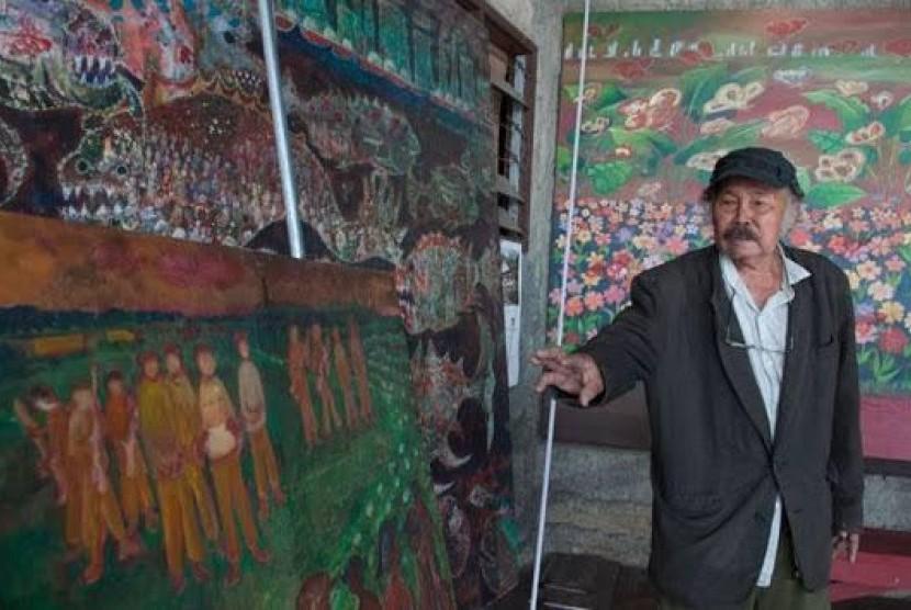 Amrus Natalsya bersama salah satu karya seninya.