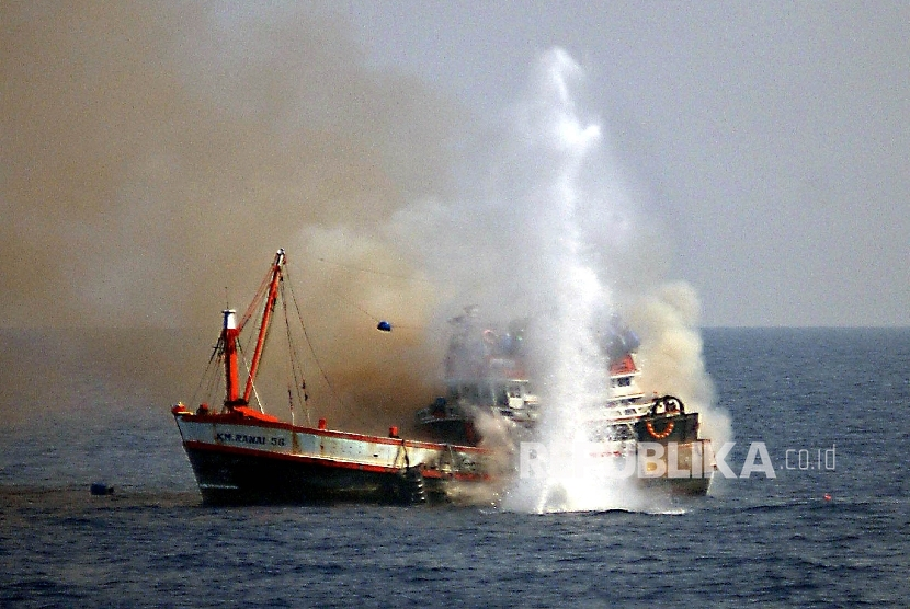 An Indonesian navy ship sinks a fishing boat from Thailand off the coast of Surabaya on November 14, 2003 after it was seized for fishing in Indonesian waters without a permit. The Indonesian navy, on a routine patrol two days ago, seized the boat and arrested 18 Thai fishermen for illegal fishing