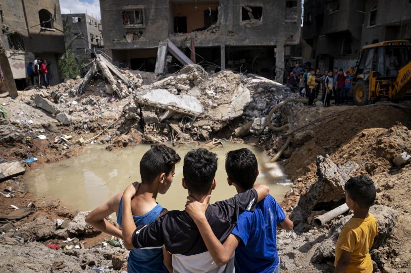 Anak-anak berkumpul di samping kawah tempat rumah Ramez al-Masri dihancurkan oleh serangan udara sebelum gencatan senjata tercapai setelah perang 11 hari antara penguasa Hamas Gaza dan Israel, Minggu, 23 Mei 2021, di Beit Hanoun. , Jalur Gaza utara.