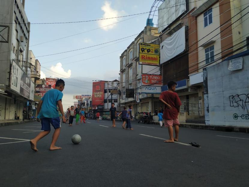 Anak-anak bermain bola di kawasan pusat pertokoan Jalan KHZ Mustofa, Kota Tasikmalaya, Rabu (21/7). Jalan itu merupakan salah satu yang ditutup oleh Satgas Penanganan Covid-19 Kota Tasikmalaya selama PPKM Darurat.