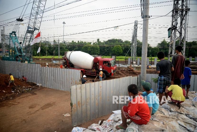 Anak-anak bermain di sekitar proyek pembangunan rel kereta api bandara di Kawasan Manggarai, Jakarta, Kamis (27/4).