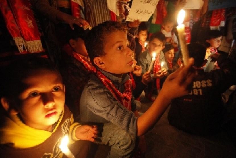 Anak-anak di Jalur Gaza, Palestina, menyalakan lilin.