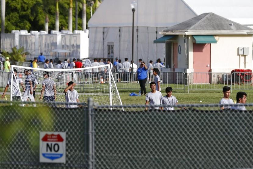 Anak-anak imigran bermain di luar kantor job Corps yang kini menjadi kediaman mereka, Senin (18/6), di Homestead Florida. Tidak diketahui apakah anak-anak yang melintas perbatasan tidak ditemani dewasa atau dipisahkan dari anggota keluarganya.