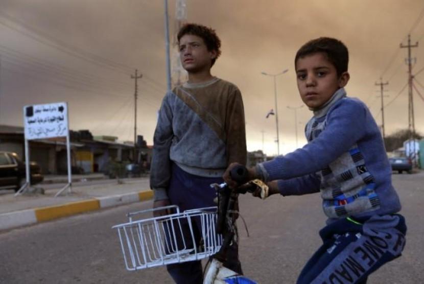 Anak-anak Irak bermain di jalan yang dipenuhi asap akibat pembakaran sumur minyak oleh ISIS di Qayyara, IraK, 12 November 2016.