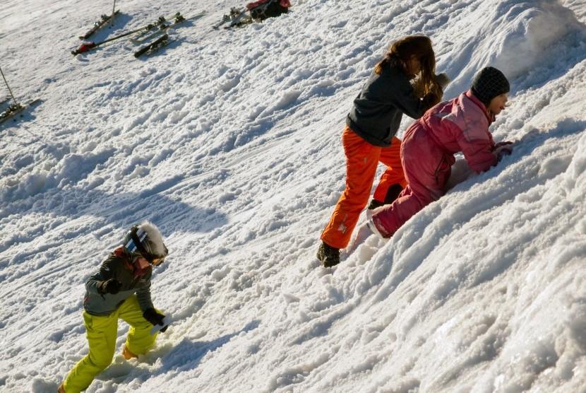 Anak-anak menikmati liburan di kawasan bersalju.