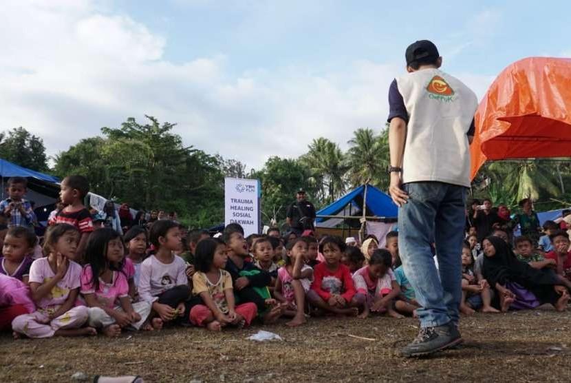 Anak-anak pengungsi menyaksikan dongeng yang dikisahkan oleh Mujani (29) dari Gerakan Pada Pendongeng untuk Kemanusiaan (Geppuk) di lapangan yang dijadikan Posko Pengungsian Desa Wombo Kalonggo, Tanantovea, Donggala, Sulawesi Tengah (Sulteng).