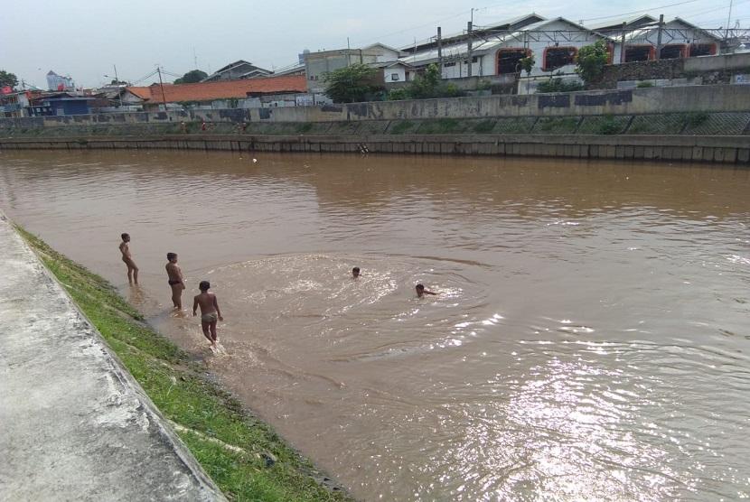 anak-anak yang tinggal di wilayah bantaran Sungai Ciliwung, Jatinegara, Jakarta Timur, memanfaatkan sungai tersebut untuk bermain dan berenang