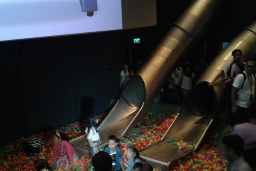 Anak bisa masuk ke dalam bioskop dengan seluncuran besar.