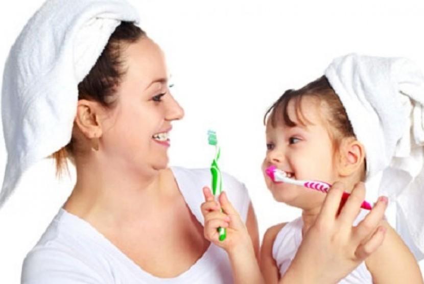 Anak dan ibu menyikat gigi